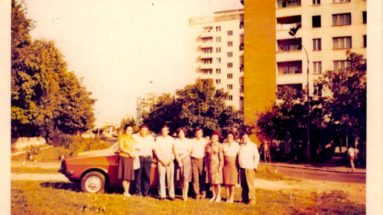 family in front of severe blocks of flats